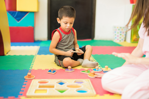 Female therapist sits with young boy on playmat, watching him practice motor control with different shaped puzzle pieces.