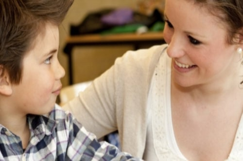 Female school-based psychologist gives encouraging smile to nervous elementary-aged boy during a therapy session.