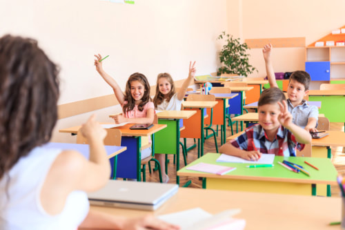 Female elementary school teacher sits at her desk and points to one of the two female and two male students with raised hands.
