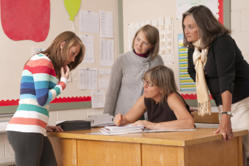 Female teacher sits at classroom desk and two female behavioral therapists stand behind, looking at high school girl with concern.