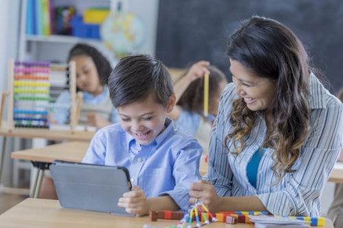 Female paraprofessional sits with elementary-aged boy in classroom as he participates in teletherapy via tablet computer.
