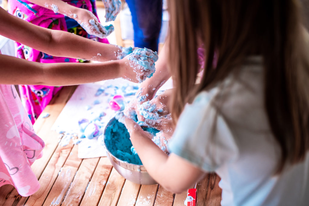 """Young school students' hands mixing and playing with brightly colored """"slime"""" for science-themed speech therapy activity."""