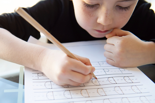 """Close-up of elementary school boy practicing handwriting by tracing rows of the letter """"D"""" on a lined worksheet at his desk."""