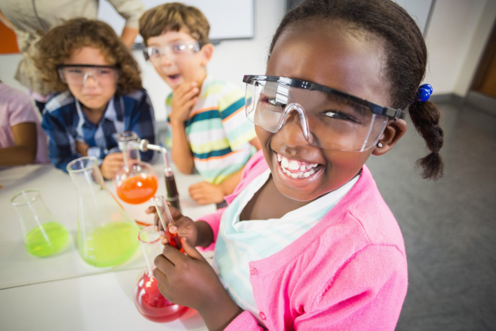 Young school girl wearing safety goggles smiles as she holds beaker of liquid during science-themed speech therapy activity.