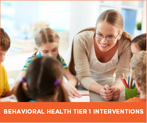 Female school-based behavioral therapist implements Tier 1 intervention, sitting at table with elementary school students.