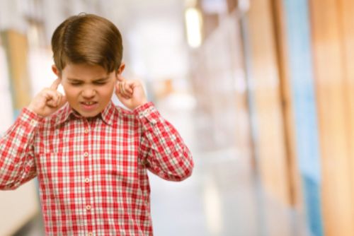 Young male student in school hallway exhibits school avoidance behavior with eyes tightly shut and his fingers in his ears.