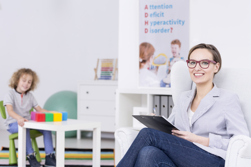 Female school-based occupational therapist sits in classroom smiling as young boy works with colorful blocks in the background.