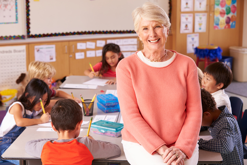 Female special education administrator smiles as children sit at desks and draw behind her.