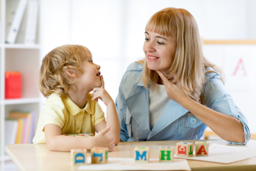 Female Clinical Fellow in school-based speech pathology job points to her vocal cords while boy practices articulation.