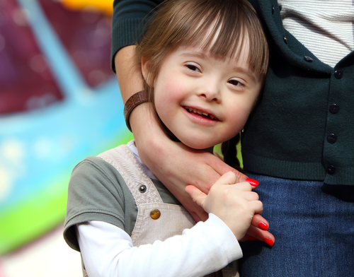 Close-up of young girl with Down syndrome facial characteristics smiling as she stands close to her mother and holds her hand.