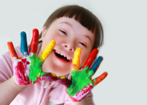 Smiling girl with Down syndrome shows paint-covered hands during extended school year (ESY) activity.
