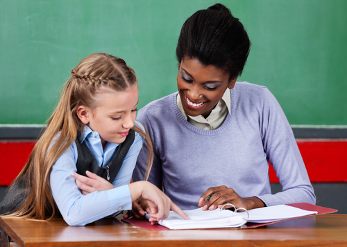 Female school-based contracted therapist sits with elementary school girl at desk in classroom as girl practices reading aloud.
