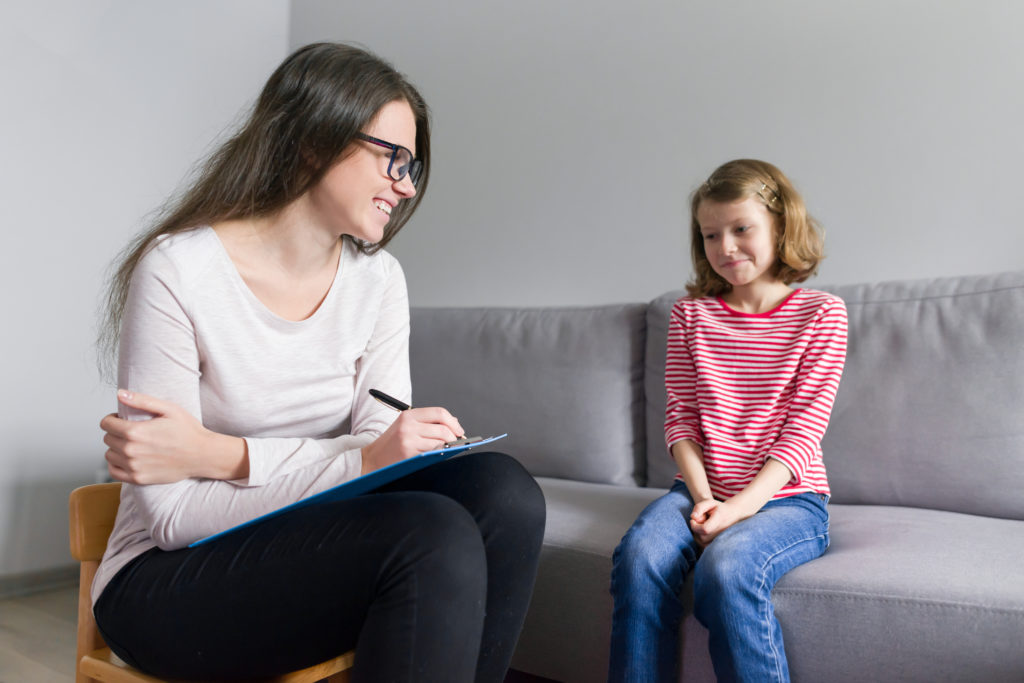 Female school-based contracted therapist takes notes on clipboard and smiles at young girl who sits on couch in therapy room.