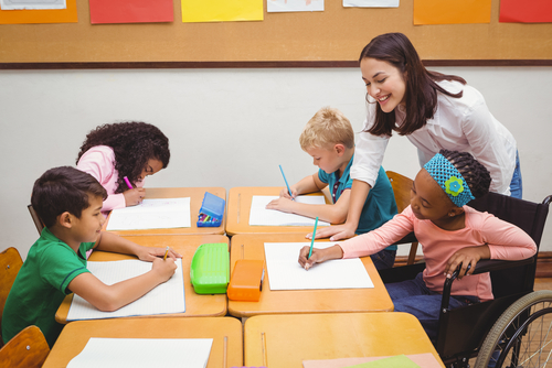Female occupational therapist supervises two male and two female elementary students seated at desks practicing handwriting.