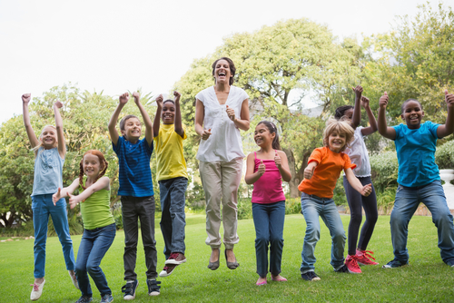 Female school-based therapist providing related services in Delaware jumping and laughing outside with eight elementary school students.