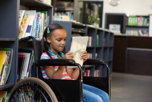 Smiling young girl in wheelchair in school library, using augmentative and alternative communication app on tablet computer.