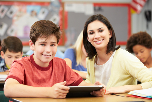 Smiling female school-based therapist sits next to a well-behaved male middle school student who is using a tablet computer.