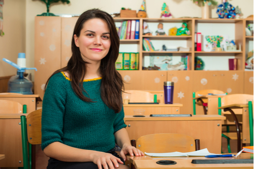 Female therapist in school-based practice in empty elementary school classroom sits at student desk, smiling at camera.