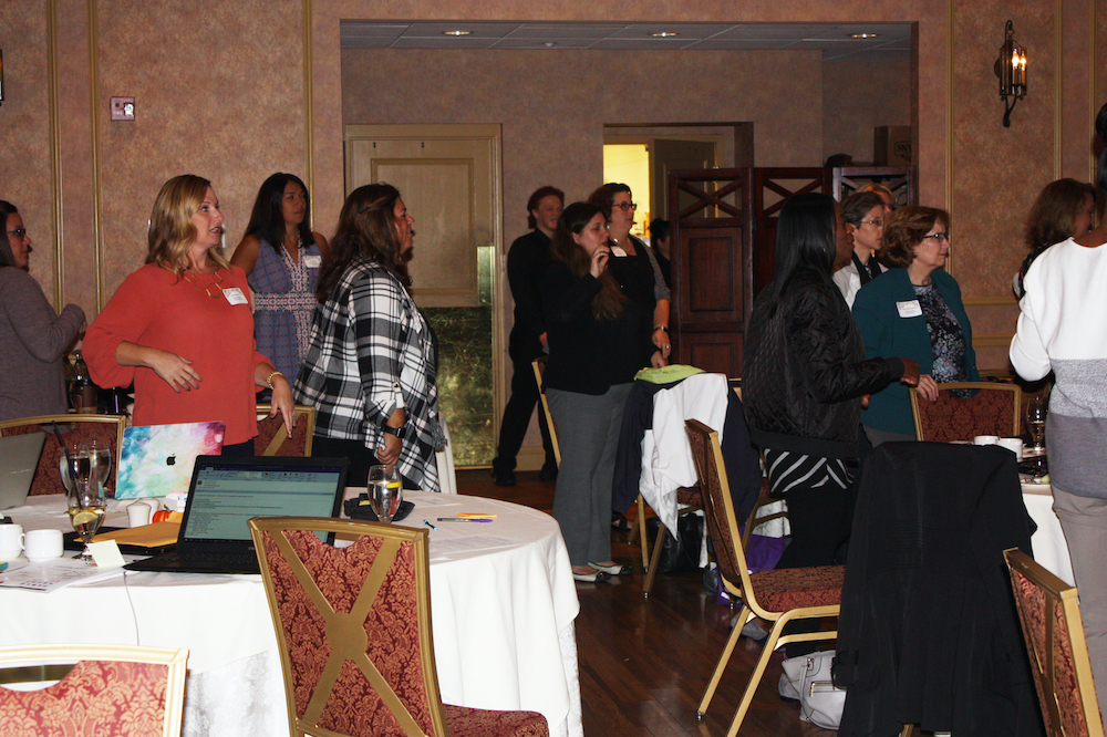 Special education administrators stand around tables in meeting room to take part in physical movement demonstration.