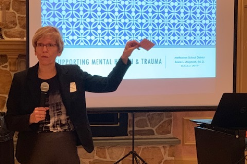 """Woman holds microphone and stands in front of screen, which displays graphic captioned """"Supporting Mental Health and Trauma."""""""