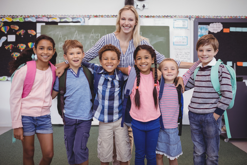 Smiling female elementary school teacher stands behind six happy students in classroom with chalkboard and bulletin boards.