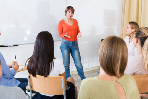 Female presenter in sweater and jeans stands to give inservice presentation to seven young teachers sitting at desks.