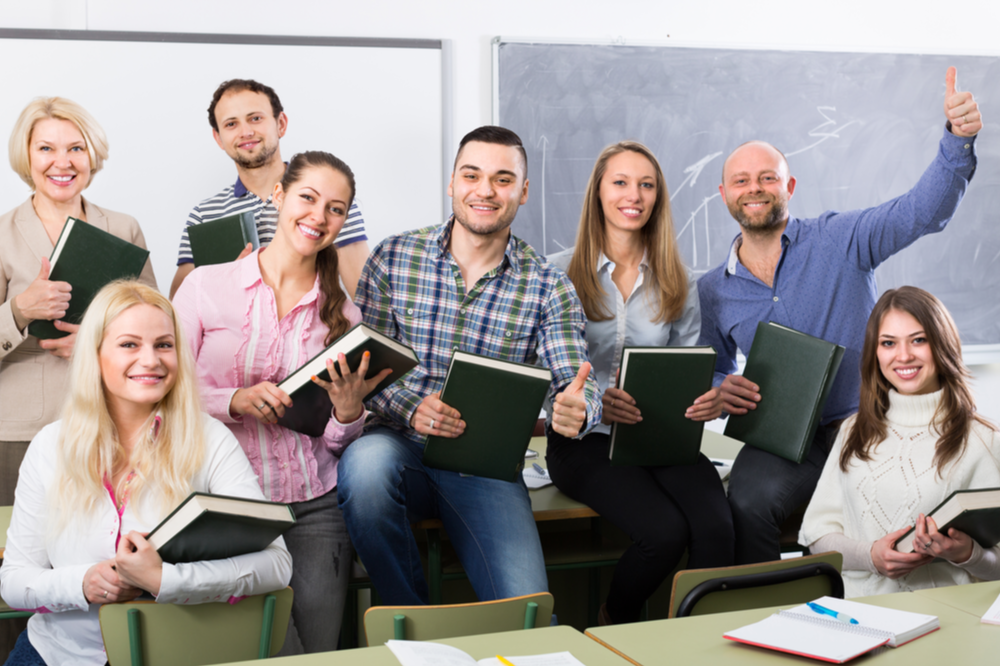 Five female and three male teachers gathered in classroom for teacher inservice training pose holding large textbooks.