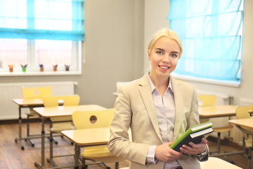 Female school-based Board Certified Behavior Analyst (BCBA) sits on a student's desk in an empty classroom, holding books.