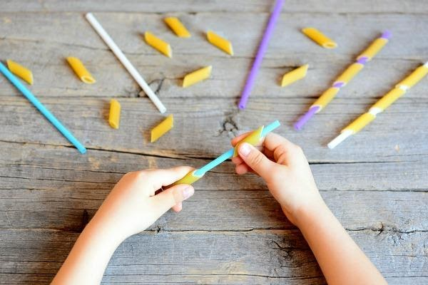View of child's hands performing arts and crafts with dried pasta and straws.