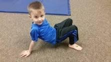 Little boy is demonstrating crab walk, his arms and legs planted on the ground and his body lifted upward.