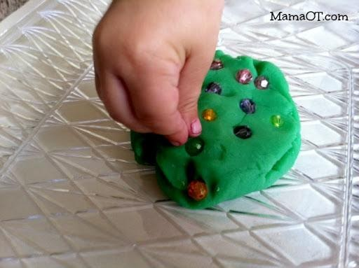 View of child's hand placing colorful beads into green play dough.