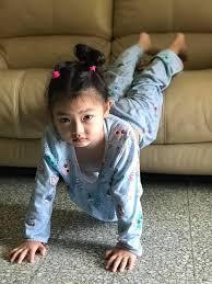 Little girl demonstrating modified plank, with feet on the couch and her hands planted on the ground.