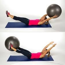 Woman laying on yoga mat demonstrating hand to foot toss with yoga ball.