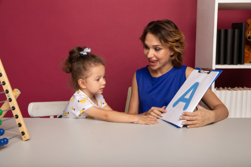 """Female school-based Speech/Language Pathologist (SLP) coaches elementary school girl to read and sound the letter """"A."""""""