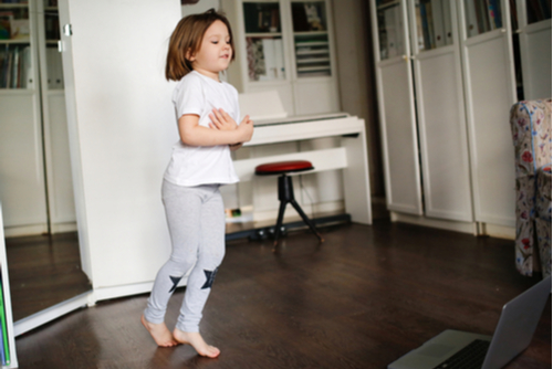 Elementary school girl dances in bedroom in front of laptop computer on hardwood floor as part of her PT teletherapy session.
