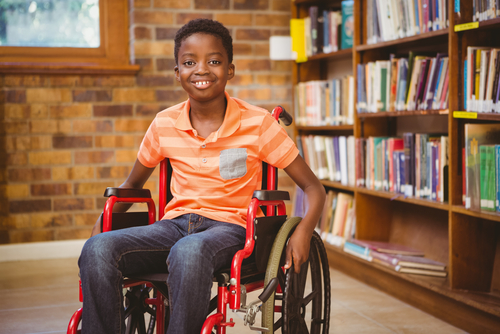 Smiling male elementary school student sits in red wheelchair in his school library, awaiting his special education therapist.