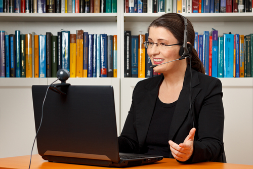 Female therapist wears a headset and sits at laptop computer with webcam mounted to screen, delivering teletherapy services.