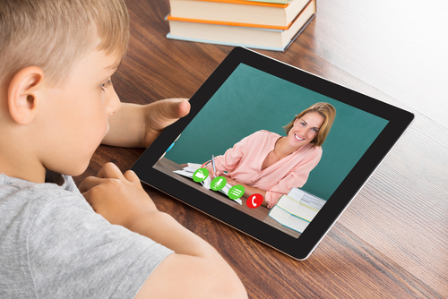 Elementary school boy sits at wooden table at home, watching therapist give instructions on tablet computer in teletherapy session.