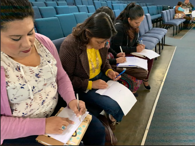 Four female teachers in Guatemala sit in an auditorium row completing worksheets as part of an inservice training for teachers.