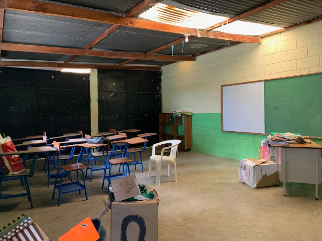 A school classroom in Guatemala is sparsely furnished with desks for students, a teacher's desk, and a bulletin board.