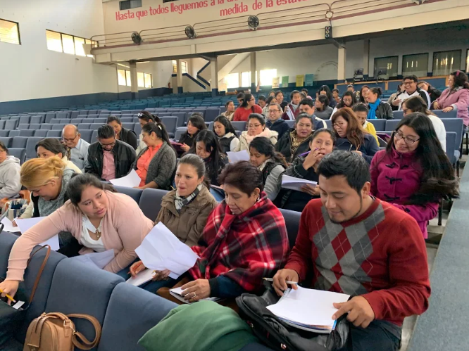 Teachers in Guatemala sit in an auditorium for an inservice training on helping students with disabilities in the classroom.