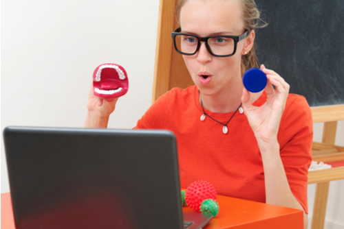 Female school-based SLP conducts teletherapy for student at home, holding model teeth and ball in view of laptop web camera.
