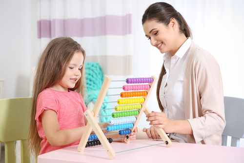 Female school-based occupational therapist sits with elementary school girl at table as girl manipulates beads on abacus.