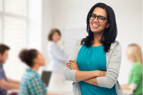 Smiling female school-based therapist stands in high school classroom, teacher and students out of focus in background.
