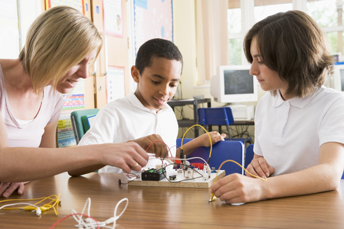 Female school-based SLP builds electronic circuit as two middle school boys describe the sequence of steps for her.