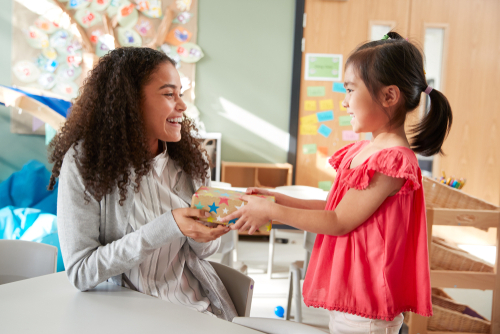 Smiling female school-based therapist in classroom receives box decorated with stickers from young girl student she helped.