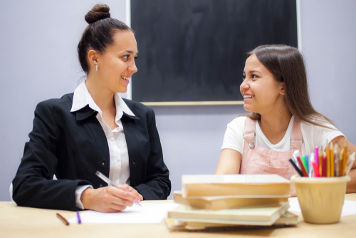 Female special education administrator and female high school student sit at desk in classroom, smiling at each other.