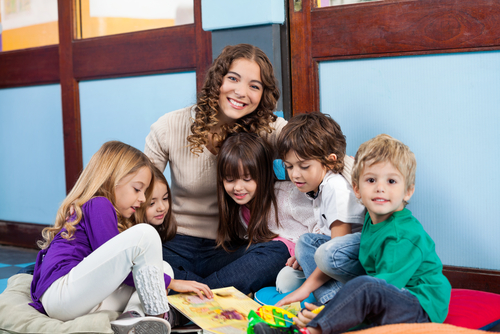 Female entry-level school-based therapist sits on floor with three young girls and two young boys looking at picture book.