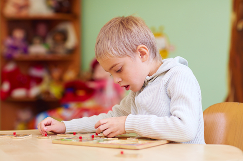 Young elementary school boy sits at table in physical therapy room and completes wooden jigsaw puzzle, toys on shelves in background.
