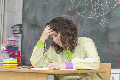 Female school-based therapist sits alone at desk in classroom, holding her right hand to her forehead, appearing distressed.